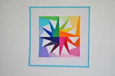 """This """"Rainbow Lake"""" mini-quilt by Diane Bohn of From Blank Pages makes fabulous use of the negative space in this circle of geese pattern. Pattern here: http://piecebynumber.com/pastbom/CircleOfGeese-PieceByNumber.pdf"""