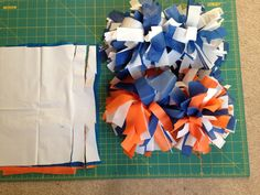 """DIY Cheerleading Pom-Poms: Easy peasy, buy plastic table cloths( I'd spring for the $1.99 ones at GFS, the dollar store ones are a little thiner, they work though). Cut plastic into 9""""x12"""" rectangles(about 20-30 sheets total.For multiple colors just layer every two), then cut long ways 4.5"""" on both sides about every inch or so, the center remains uncut, gather the center and tape tightly with duck table or electrical tape. Then fluff it by pulling in opposite directions and scrunching."""