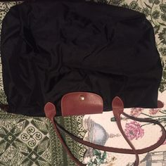Large Longchamp Le pliage tote Authentic Authentic well loved and used Black Tote. Great everyday bag to fit all your necessities.  Small holes in each corner on the bottom, some light wear.  Handles and leather in great shape.  Please comment me for questions and check out photos! Longchamp Bags Totes