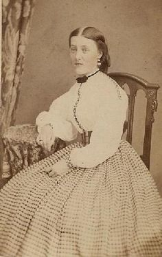 Pretty lady in checked skirt and white blouse. Early 1860's