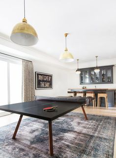 In the media room, a chic Ping-Pong table from sits on top of a Shoppe by Amber Interiors rug. Thomas O'Brien brass pendants from Circa Lighting ensure there's plenty of light for late-night games. In the back, Jayson Home stools are pulled up to the bar. Teen Game Rooms, Small Game Rooms, Family Game Rooms, Family Games, Ping Pong Room, Ping Pong Table, Pool Table, Game Room Design, Family Room Design