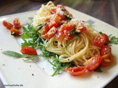 Leckere Nudeln, Pasta auf Rucola mit Knoblauch und Tomaten
