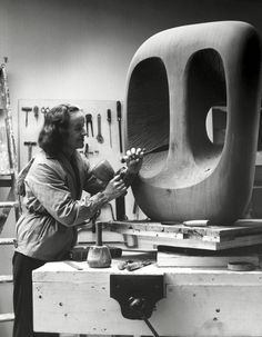 Exhibition: 'Barbara Hepworth: Sculpture for a Modern World' at Tate Britain, London. http://artblart.com/2015/10/21/exhibition-barbara-hepworth-sculpture-for-a-modern-world-at-tate-britain-london/ Photo: Val Wilmer. 'Barbara Hepworth in the Palais de la Danse studio, St Ives, at work on the wood carving Hollow Form with White Interior' 1963