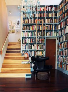 The library and double-height hallway in an architect's house in Los Feliz, California. The bookshelves, probably 14 feet tall, are painted blue (to match the chandelier?) and the taller shelves are accessed by an extra-tall rolling library ladder. Floor To Ceiling Bookshelves, Bookshelves Built In, Book Shelves, Bookcases, Book Storage, Bookshelf Wall, Built Ins, Library Shelves, Bookcase Stairs