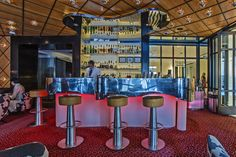 Spivak Architects - The Mark Restaurant by Jean-Georges. Chrome mirror-finish custom organic shape bar, Chrome flush-mount lights on veneer ceiling & walls.