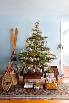 A cozy Christmas in the country requires (battery-operated) candles plus wooden ornaments. Round out the scene with a pair of old-fashioned snowshoes and bottle-brush trees in place of a skirt. Click for more Christmas tree decoration ideas.
