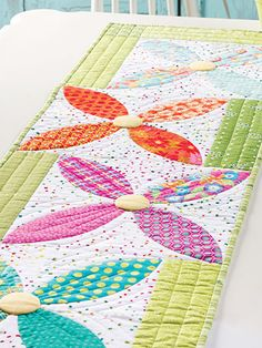 """Sprinkle a field of wildflowers on your table when you stitch this fun table runner that uses the classic Orange Peel block. This e-pattern was originally published in the summer 2016 issue of Quilter's World magazine. Finished size is 66"""" x 1..."""