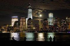 Imagen del anochecer de ayer, 1 de octubre de 2012, en la que se aprecia la luna elevandose detrás de la línea del horizonte del Bajo Manhattan de Nueva York y One World Trade Center, mientras algunas personas aprecian el panorama sobre el Río Hudson en Jersey City, New Jersey