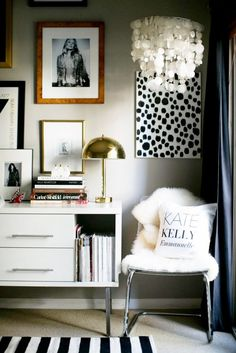 Cozy chair in corner of office surrounded by chic gallery wall and decorative chandelier