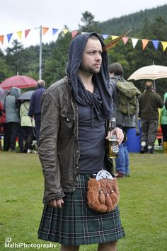 Kilt and leather jacket with scarf.