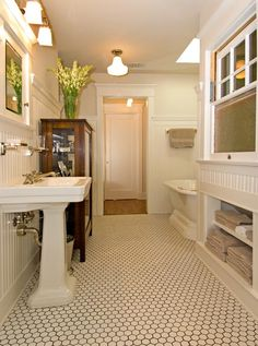 bead board, hex floor but with lighter grout, built in towel storage but with cabinet doors, and glass shelf above sink but still under top of bead board