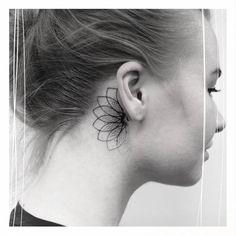 Single needle style half mandala tattoo behind the right ear.