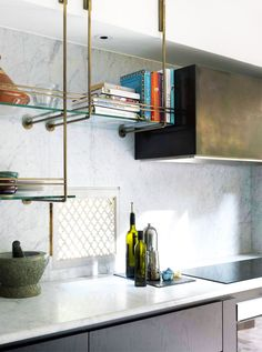 brass pipe and glass kitchen shelves with marble tiled wall backsplash