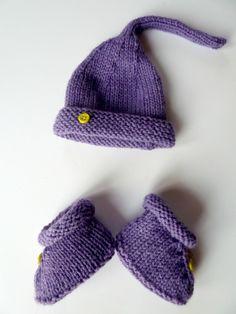 $25 Violette est un ensemble Bonnet et Chaussons réalisé en tricot tenant bien au chaud les petites extrémités de bébé. Idéal pour l'hiver, l'automne et le printemps, tout a été réalisé en point jersey et en laine acrylique. L'ensemble est ornés de petits boutons jaune. Il s'agit d'une taille naissance.