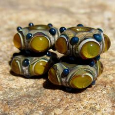 Lampwork glass set with amber bubble windows built on base dots of dark ivory with its distinctive crackle quality. Marine blue contrasting accent dots.