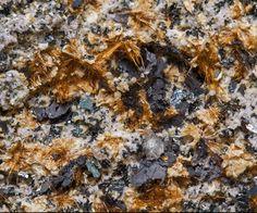 Yuanfuliite, (Mg,Fe++)(Fe+++,Al,Mg,Ti,Fe++)(BO3)O, Hematite, Calcite, Nuestra Señora del Carmen Mines, La Celia, Jumilla, Murcia, Spain. Dimensions: 3.6 x 2.8 x 2.5 cm. Felted aggregates of acicular to fibrous, bright, honey-colored Yuanfuliite crystals, on a rocky (lamproite) matrix, with Hematite and white spheroidal Calcite growths. Copyright: © fabreminerals.com