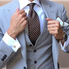 Look the best you possibly can in a grey three piece suit and a white dress shirt. Shop this look on Lookastic: https://lookastic.com/men/looks/three-piece-suit-dress-shirt-tie/21709 — White Dress Shirt — Dark Brown Polka Dot Tie — White Pocket Square — Grey Three Piece Suit — Silver Watch