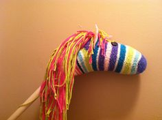 Em's Hobby Horse    Stuff a fuzzy sock with filling.  Add eyes, ears, and attach yarn mane (approximately 40 strands of yarn of various sizes).  Place sock over dowel and tuck under a bit.  Hot glue the sock to the dowel.  Gallop away!