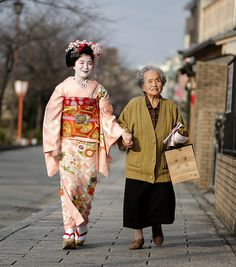 Kyoto, Japan. On her first day, a trainee geiko (the Kyoto word for geisha) is led round the tea houses of the Miyagawa-cho district to be introduced. The lady with her is carrying a bag of flyers to announce her debut and professional name, Toshichika. Some of the flyers can be seen in her hand.
