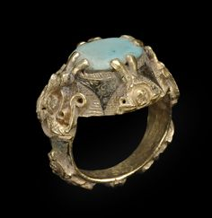 Ring fabricated from gold and set with a turquoise, the sides with appliqués in the form of a double-bodied harpy, engraved and inlaid with niello. Eastern Iran, 5th century AH/11th century CE