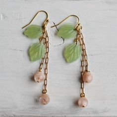 These beautiful and ususual earrings are made from vintage milky green glass leaves, with little peach glass berries on gold plated chain. The colours are so delicate and beautiful together.  The leaves measure about 15mm (just over half an inch) long and the length of the whole earring is about 70mm (three inches). The earrings are gold plated.