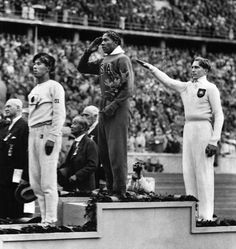 Jesse Owens salutes during the presentation of his gold medal for the long jump on August 11, 1936, after defeating Germany's Lutz Long during the 1936 Summer Olympics in Berlin