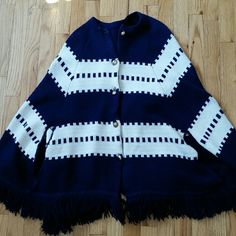 Vintage Knit Navy Striped Poncho Cape This piece is adorable!  One size fits most. Brass colored buttons.  Holes on side for arms. Very warm.  Fringe along bottom.   Needs a little tlc on the buttons, brass is scraping off and some stitching issues around the buttons.  New owner might want to close button holes a little more so buttons don't slip out.  One spot as shown on photo. Otherwise a great piece! Sweaters Shrugs & Ponchos
