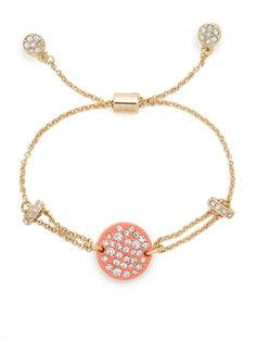 This gorgeous bracelet features delicate gold chains and a coral disk accent, sure to catch anyone's eye. The highlight here? All those glittering and glamorous pavé crystals.