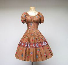 Cute Vintage 1960s Cotton Rockabilly Dress with a festive print of red and blue flowers on a brown background.