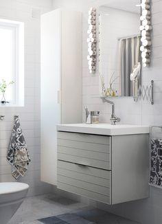 Baño pequeño de color blanco con un armario alto blanco, un espejo y un mueble de lavabo gris con dos cajones.