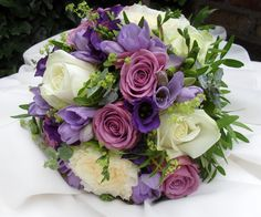 A hand tied bouquet of white roses, lilac 'Coolwater' roses, freesia and lisianthus by Orchard Designs