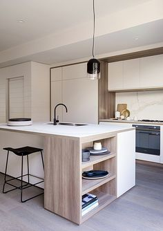 really love the storage at the end of the island in this minimal contemporary kitchen
