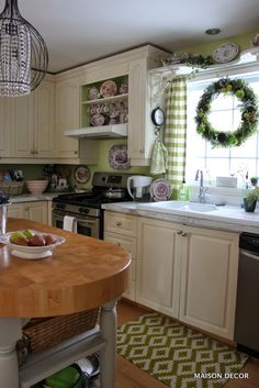Add personality to a kitchen using color and unique accents like a pocket watch clock hung on the side of the cupboard. A zippy green and white rug and hand towels finish off  the space. All found at HomeGoods. Sponsored pin by Happy by Design.