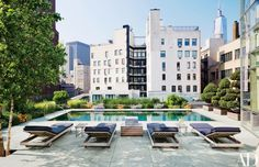 The slate-paved pool terrace is furnished with Summit tables and chaise longues | archdigest.com
