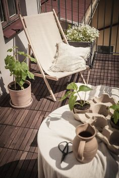 SMALL BALCONY WITH DECK CHAIR AND GREEN PLANTS. A warm Gothenbugh apartment with tactile art and beige aesthetics. A nice collection of abstract wall art and modern sculptures. See the home tour of this stunning Scandinavian apartment on Nordic Design Blog Hege in France.  #scandinavianliving #hometour #tactileart #abstractart #beigeaesthetics