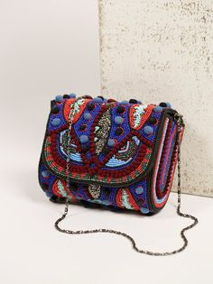Gorgeous beaded crossbody with cute pompom accents throughout. Removable chain strap. Magnetic closure. Lined inner with mirror panel.