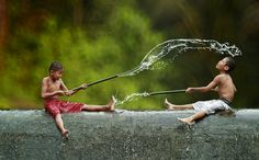 Indonesian kids playing with hand made water guns.