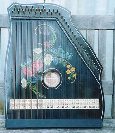 zither- a plucked musical instrument consisting of numerous strings stretched over a resonating box, a few of which may be stopped on a fretboard or fingerboard.