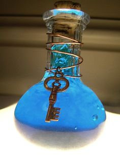 Mana / Magic / Blue Potion. Thick glass bottle, about 3.5 - 4 inches tall. Difficult to break due to thickness (about 1/4 inch). Cork is about 1/2 inch in diameter at most and 3/4 inch tall. Copper wire and skeleton key. The stuff inside is gooey, has neat air bubbles and is a deep shade of blue. Looks awesome in the sunlight! :3 Magic potion from such and such series, used in that movie to give the character increased turbo speed and legs of awesome. Also ma...