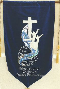 International Christian Dance Fellowship Banner made in Oamaru, New Zealand in 1991 for the 1st ICDF Conference in Jerusalem, Israel.  It is in royal blue velvet with silver lamé cross and figures, blue sequinned satin river, with the world represented by corded globe...