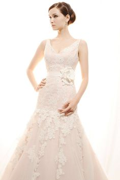 BL012-Gorgeous tank style V-neck gown in Lace and Tulle. The lace has been delicately beaded throughout with ivory sequins and accented at the natural waistline with a grosgrain ribbon belt and floral corsage. The circular cut tulle skirt leads into a chapel length train. Available in white, ivory, or in combination w/rose.