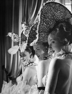 Showgirls (L-R) Dawn McInerney, Thana Barclay and Joy Skylar in costume wearing ornate hats at the Latin Quarter nightclub. Photograph by Gjon Mili. New York City, 1947.