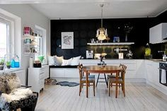 Keittiö, joka ei äkkiseltään näytä keittiöltä. Vasemmalla löhönurkkaus ja seinä näyttää mustalta tapetilta. Pöytä sopii, vaikka eri tyyliä kuin muuten. Kiva kokonaisuus.