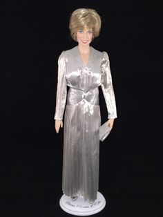 This Franklin Mint Diana doll is wearing a custom replica of the silver lame' pleated dress designed by Bruce Oldfield that Princess Diana wore for a fashion show gala in Melbourne March 1985.