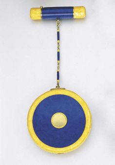 AN ART DECO ENAMEL POWDER COMPACT AND LIPSTICK HOLDER    The 14k gold circular case with blue and yellow enamel imitating lapis lazuli and marble, opening to reveal a fitted mirror, to the enamel link chain and cylindrical lipstick holder of similar design, circa 1925, 14.2 cm. high