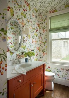 Green and orange powder room features a green trellis wallpapered ceiling, Cowtan & Tout Bamboo Wallpaper, over walls clad in Thibaut Fishbowl Wallpaper lined with an orange washstand topped with white quartz fitted with an oval sink and a deck mount vintage faucet and an oval faux bois mirror, Warbler of The Woods faux Bois Mirror Oval.
