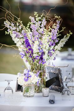 Purple Lavender and White Centerpiece: Mason jars of white hydrangea, purple iris, lavender sweet peas and dried lavender are reused on the reception tables to accent the stunning taller centerpiece of white, lavender, and purple larkspur and curly willow by Andrea Layne Floral Design (www.andrealaynefloraldesign.com)