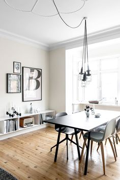 Black and white art in dining room with industrial light fixture