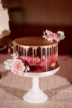 Burgundy painted wedding cake with gold drip and gold leaf, topped with pink flowers. #goldweddingcakes