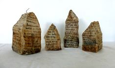 Ines Seidel wire houses, with or without a concrete base. Wrapped in spontaneous text written on tea bags, sealed with wax.